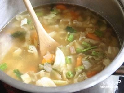 Берем большую кастрюлю и вливаем в неё 2 литра воды. Когда вода закипит выкладываем морковь и варим 5 минут. Уменьшаем температуру огня, добавляем лук, капусту, сельдерей и варим ещё 10 минут.