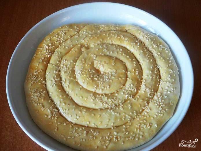 На смазанную растительным маслом форму для запекания выложите все трубочки поочерёдно по спирали. Следите, чтобы тесто нигде не порвалось. Смажьте пирог яичным желтком, посыпьте кунжутными семенами и отправьте выпекаться в духовку на полчаса при температуре 180 градусов.