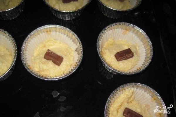 3.В подготовленные формы, положите по одной столовой ложке теста сверху, слегка надавливая, разложите по кусочку шоколада.