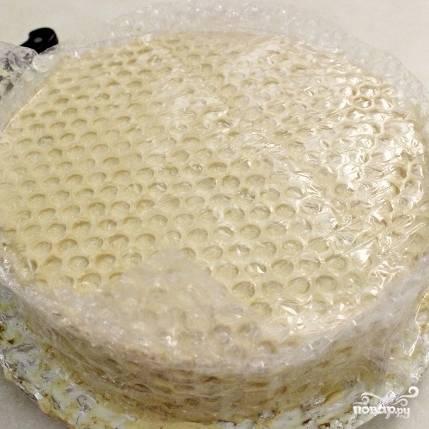 14. Желатин добавьте к смеси из сгущенки, сметаны и масла. Перемешайте и готовой массой покройте торт. Затем сразу же прижмите на крем пузырчатую пленку пузырьками в крем. Так мы сделаем соты. Действовать надо очень быстро, пока крем не застыл.