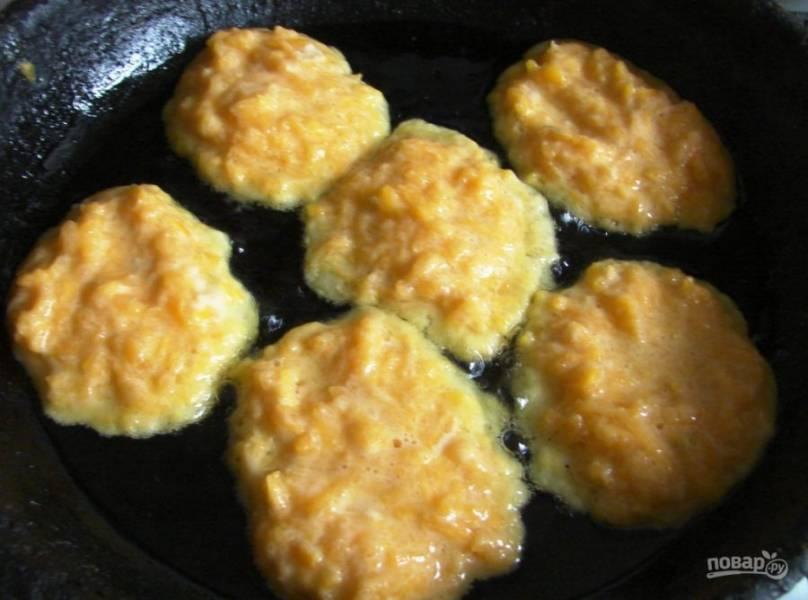 Разогрейте масло на сковороде. Вливайте в неё большой ложкой тыквенное тесто.