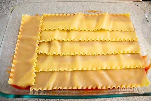 Дно формы залейте тонким слоем томатной пасты, затем - слой макарон.