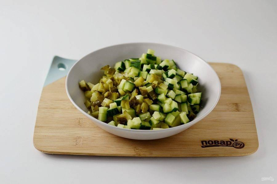 Добавьте нарезанные кубиками свежие и соленые огурцы.