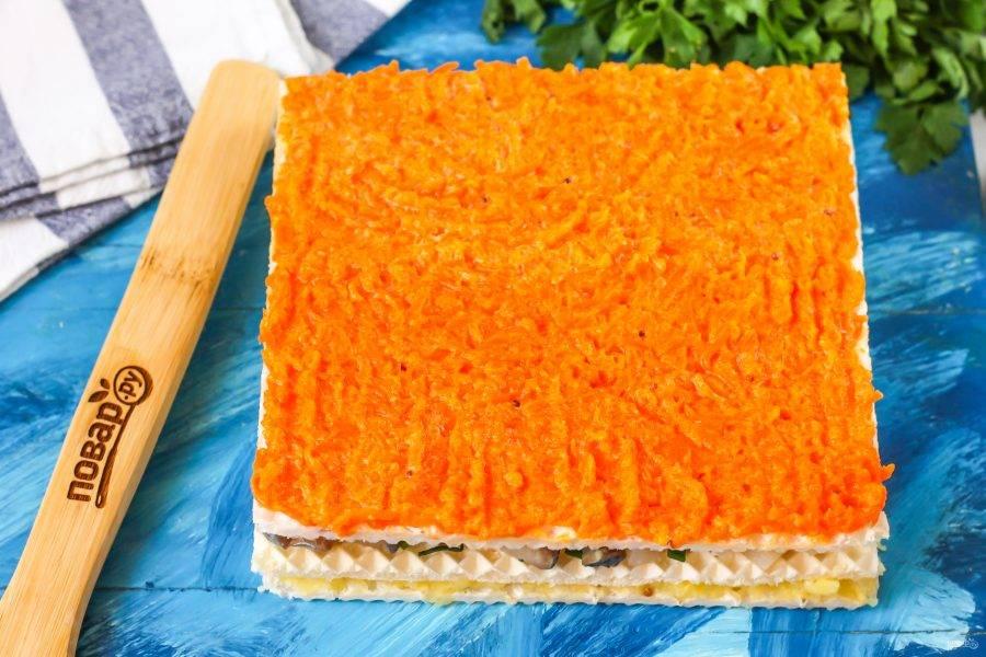 Выложите на вафельный корж морковный слой, тщательно разровняйте. Выложите корж с морковью на селедочный слой.