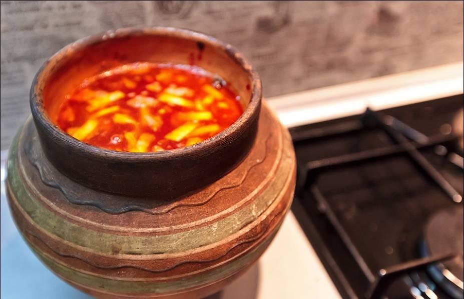 Перемешиваем содержимое горшочка, добавляем томатную пасту и вливаем бульон. Добавляем кусочки мяса.