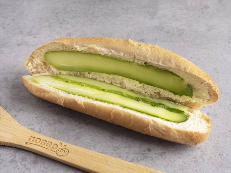 Огурец нарежьте тонкими пластинами с помощью овощечистки. Выложите внутрь багета на обе части.