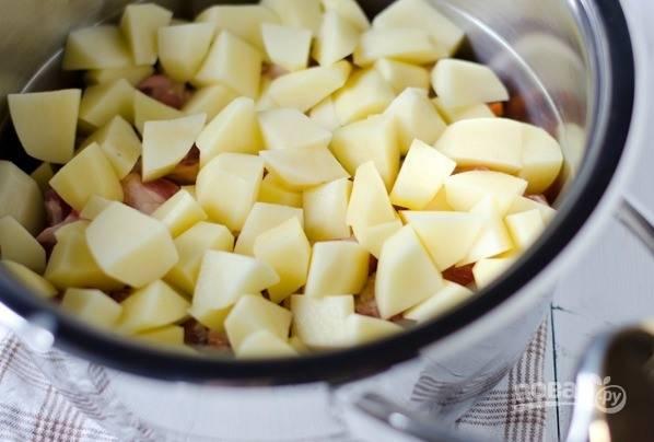 Теперь настала очередь картофеля. Вымойте его максимально тщательно и очистите от кожуры. Нарежьте на одинаковые по размеру кусочки (чуть меньше, чем куски мяса). Положите его на свинину в кастрюльку.