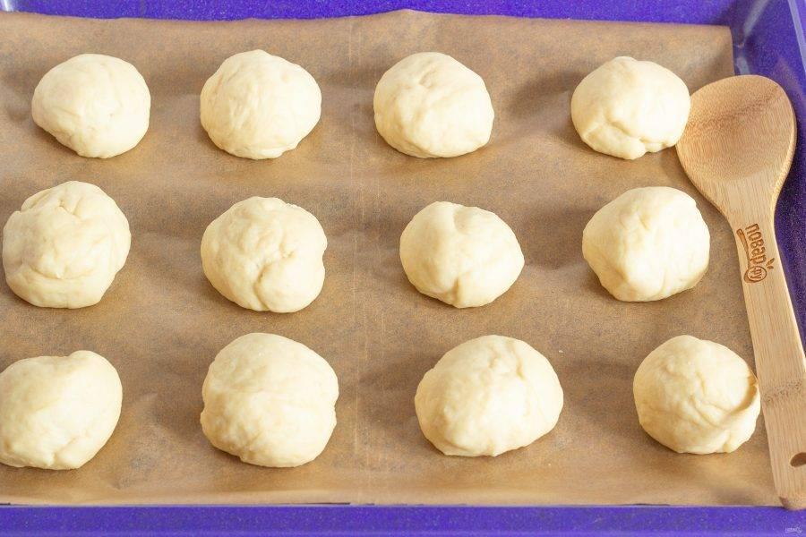 Выложите заготовки на противень с пекарской бумагой, накройте и снова поставьте в теплое место на 20-30 минут.