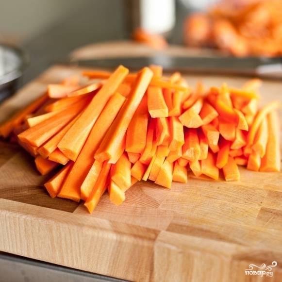 2. Поставьте на плиту воду с солью. Доведите до кипения. А в это время приготовьте морковку. Очистите ее и нарежьте брусочками.