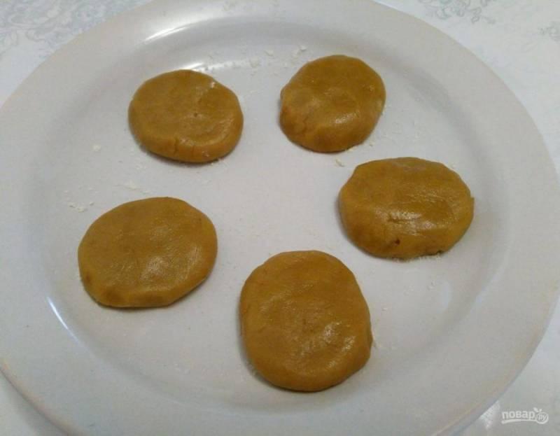 Отщипывая от получившегося теста небольшие кусочки, скатайте из них шарики размером с грецкий орех и разместите по краям плоской тарелки, слегка присыпанной мукой. Придавите шарики, формируя круглое печенье, и выпекайте на мощности 80% в течение 2 минут. При выборе максимальной мощности проверьте готовность печенья спустя 90 секунд.