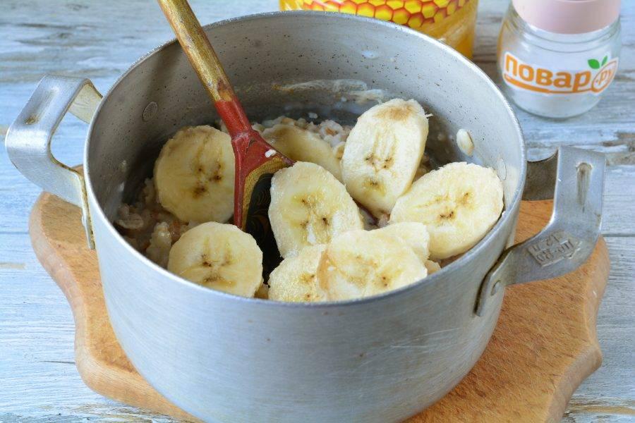 Добавьте в кашу нарезанный колечками банан и перемешайте. Томите кашу на тихом огне еще минуту.