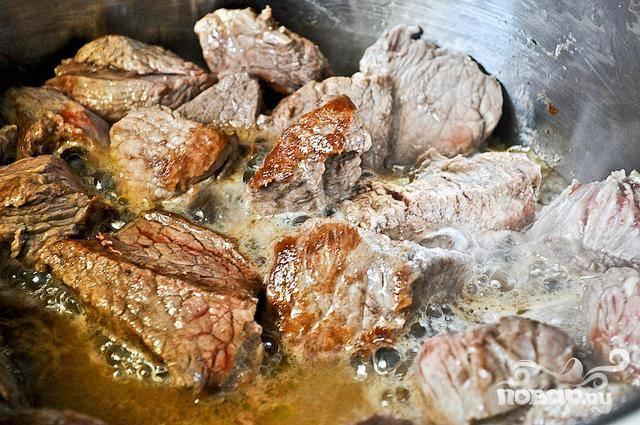 1. Нарезать говядину кубиками. Нарезать луковицу средними кубиками. Измельчить чеснок. Нарезать морковь кружками. Нарезать картофель большими ломтиками. Нагреть большую кастрюлю на среднем огне. Добавить оливковое масло. Обжарить нарезанную говядину течение 3 минут в масле до коричневого цвета.