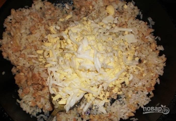 Яйца отварите вкрутую. Натрите их в фарш, а также добавьте рис с солью и перцем. Перемешайте и жарьте 5 минут.