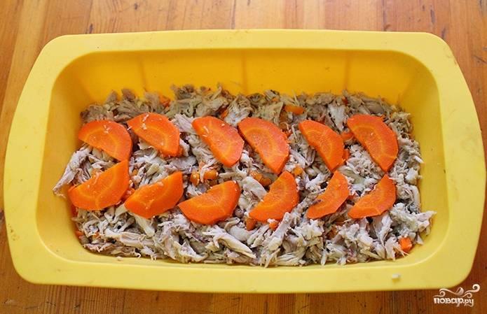 Положите мясо на дно формы для холодца, украсьте его морковью, положите чеснок и несколько горошин перца, можно украсить зеленью.