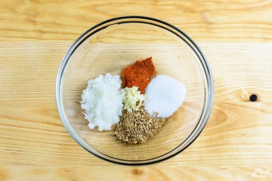 1. В глубокой мисочке смешайте мелко порезанный репчатый лук, продавленный через пресс чеснок, молотые семена кориандра, паприку, чили и соль.