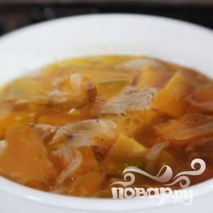 Чистим, нарезаем клиньями картофель, морковь и тыкву. Давим чеснок, грубо нарезаем лук. Затем нагреваем масло в кастрюле. Добавляем чеснок и лук. Обжариваем до полупрозрачности лука. Залить бульон, положить картофель, морковку и тыкву нарезанные небольшими кусочками. Посолить, поперчить и довести до кипения. Уменьшите огонь, накрыть крышкой и кипятить на медленном огне около 20 минут
