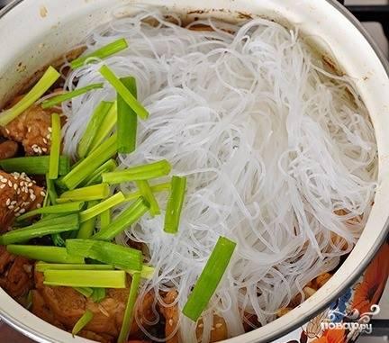 Когда блюдо будет почти готово, влейте в кастрюльку с курицей и овощами кунжутное масло а также всыпьте кунжут. Положите заранее замоченную и набухшую стеклянную лапшу. Зеленый лук вымойте и нарежьте соломкой. Бросьте его в кастрюлю. Томите блюдо под крышкой до полной готовности три минуты.