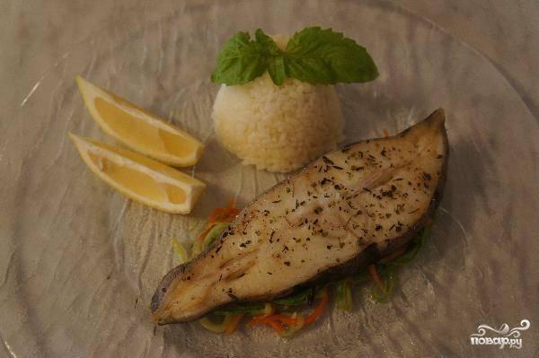 На тарелку выкладываем немного овощей, сверху укладываем стейк из палтуса. Подавать можно с рисом, украшать - лимоном. Готово!