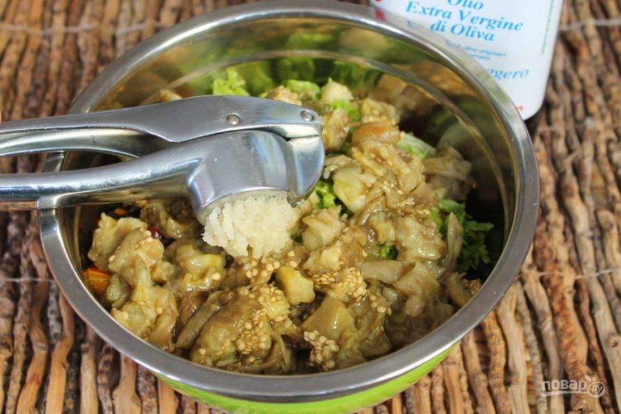 В салат добавляем оливковое масло, немного соли и пропущенный через пресс чеснок. Все перемешиваем.