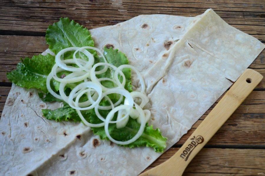 Лист лаваша разложите на рабочей поверхности. По желанию его можно смазать кетчупом или майонезом. Затем выложите листья салата, маринованный лук.