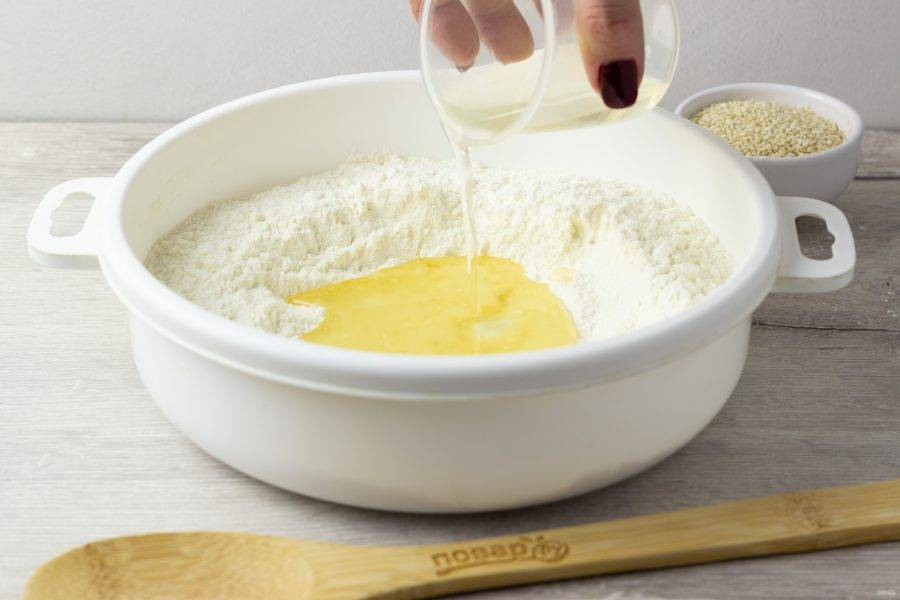 Сделайте в муке лунку и влейте масло, воду и лимонный сок.