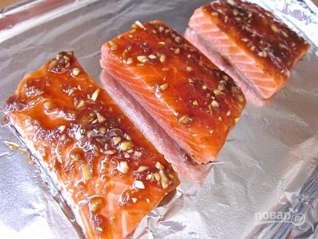 5.Выложите лосося кожей вниз на противень, застеленный фольгой, сверху выложите маринад.