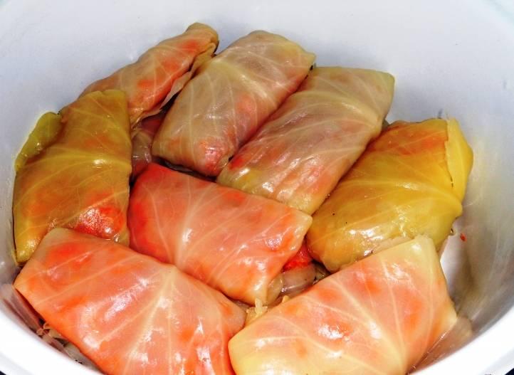 В капустные листья положите часть морковной начинки и заверните как голубцы. Сложите в кастрюлю.