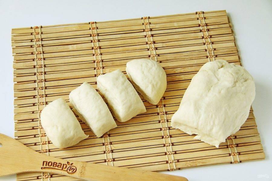 Тесто необходимо обмять и разделить на две части. Каждую часть раскатайте в колбаску и разрежьте ее еще на 4 части.