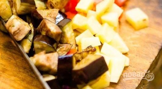 Почистите картофель, с помидоров снимите кожицу и нарежьте кубиком. Вместе с готовыми баклажанами сложите овощи в кастрюлю к луку и чесноку.