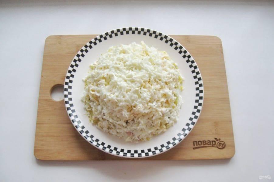 Белок яиц натрите на терке или помните вилкой. Покройте верх салата.