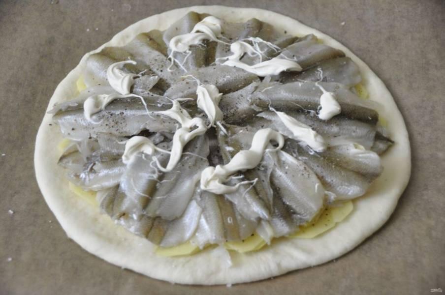 Сверху на картофель выложите корюшку, добавьте немного жирных сливок или кусочки сливочного масла.