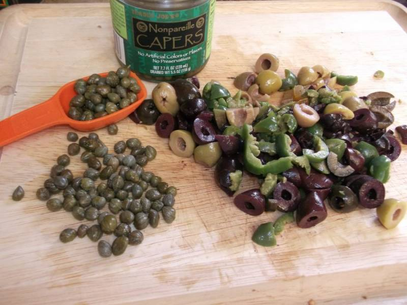 6.Оливки разрежьте на 2 части, добавьте их и каперсы к соусу, по вкусу посолите и поперчите, добавьте хлопья красного перца.
