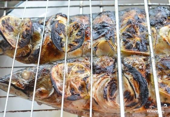 Когда угли будут готовы, размотайте рыбу и выложите ее на решетку для барбекю прямо с колечками лайма и лука. Обжаривайте рыбу с каждой стороны по десять минут до полной готовности.
