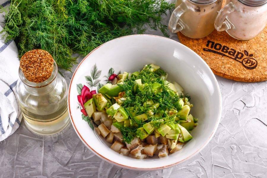 Авокадо промойте в воде, разрежьте пополам, удаляя косточку. Счистите кожуру и нарежьте мякоть плода кубиками. Промойте зелень укропа и выложите обе нарезки в емкость.