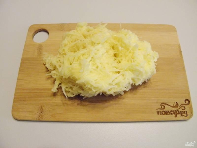 Очистите картофель. Натрите его на мелкой терке, отожмите руками от сока.