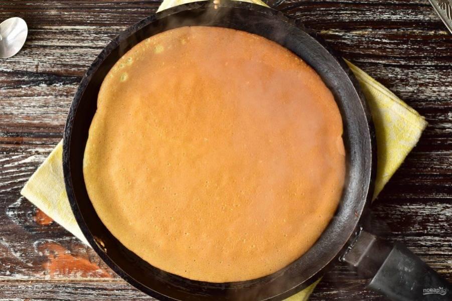 В сковороду налейте половником тесто. Жарьте блины до красивого и румяного цвета.