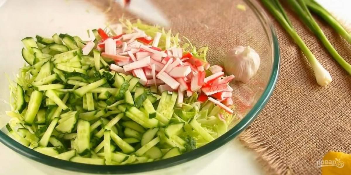 1. Капусту нашинкуйте соломкой, свежие огурцы и крабовые палочки также нарежьте соломкой. Зеленый лук нарежьте тонкими кольцами.