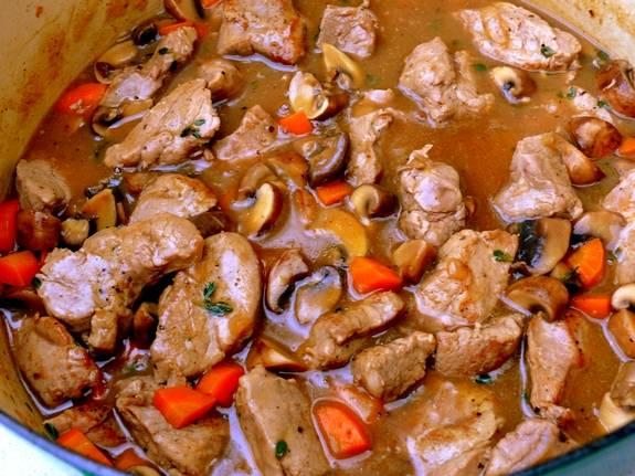 6. Крахмал развести в небольшом количестве бульона. На сковороду с обжаренными овощами отправить свинину. Влить крахмал, немного вина и бульона. Довести до кипения и посолить, поперчить по вкусу. Накрыть крышкой и тушить до готовности мяса. При необходимости подливать на сковороду бульон, чтобы мясо не горело.