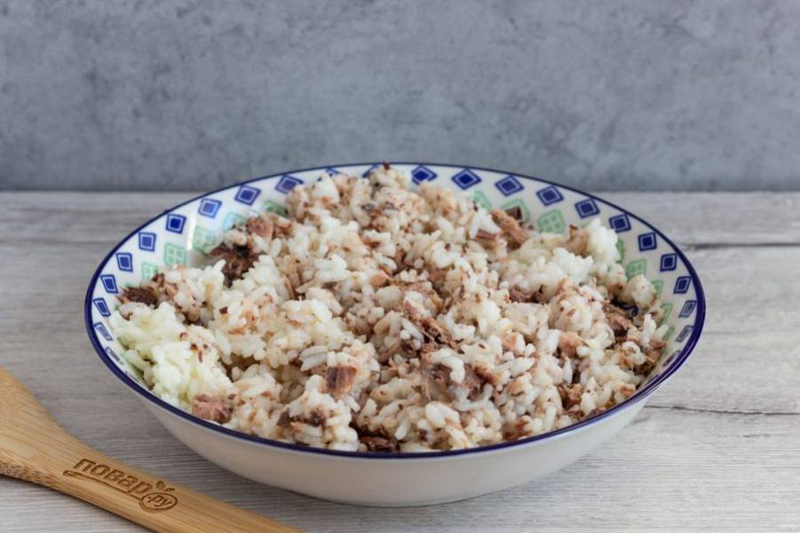Кусочки тунца освободите от костей и разомните вилкой. Смешайте с вареным рисом.