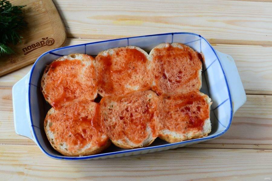Разрежьте булочки вдоль пополам, положите в форму, подходящую по размеру. Смажьте булочки любым томатным соусом.