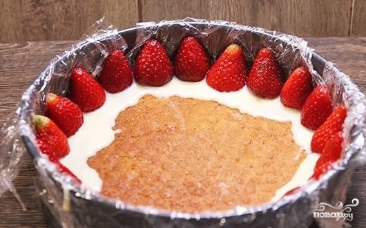 12. Форму для торта застелите пленкой. Уложите первый корж. Пропитайте его клубничным сиропом. Выложите небольшую часть крема. По кругу уложите клубнику, разрезанную вдоль. Пространство заполните еще одной частью крема.