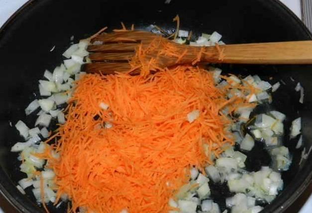 3. Морковь натрите на крупной терке. Растопите сливочное масло на подогретой сковородке и поджарьте лук и морковь.