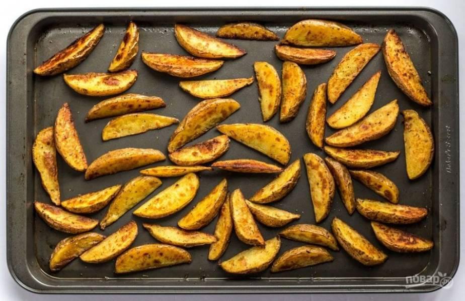 4. Поставьте противень в заранее разогретую до 200 градусов духовку и запекайте в течение 30-35 минут до золотисто-коричневого цвета. Не забывайте периодически помешивать картошку во время приготовления, чтобы она не подгорела и равномерно зарумянилась.