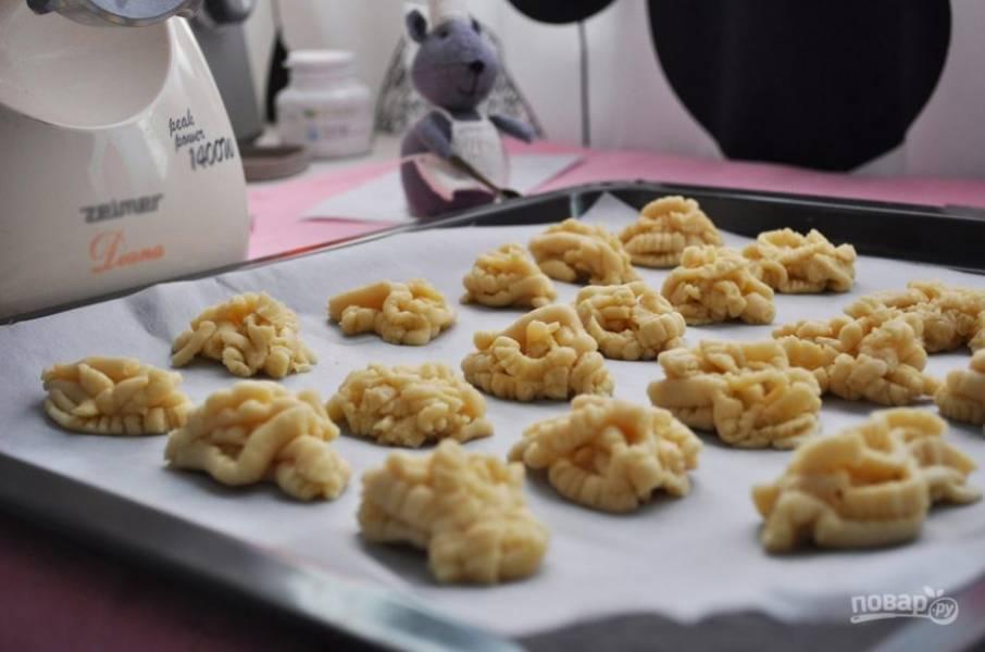 6. Отрезайте ножом тесто и выкладывайте небольшие печеньки на противень, застеленный пергаментом. Отправьте в разогретую до 200 градусов духовку.