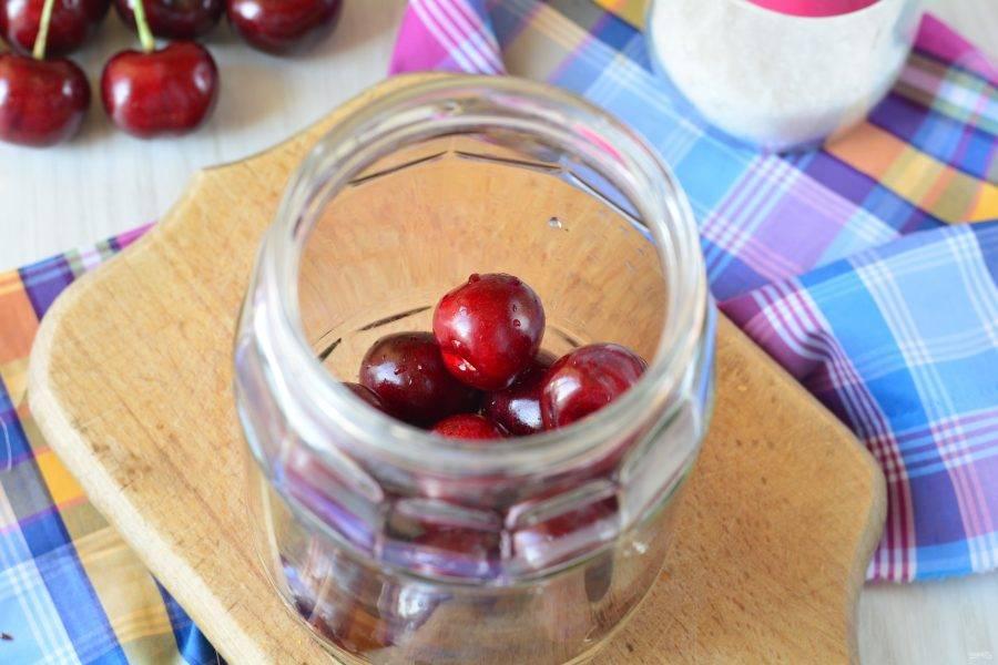 Промойте черешню, удалите все хвостики. Выложите ягоды в чистые банки.