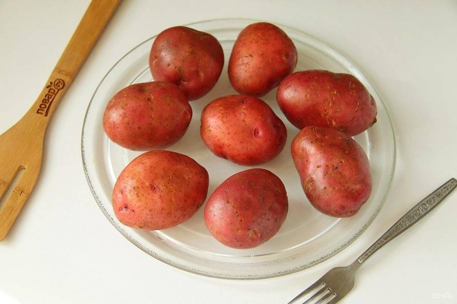 Картофель хорошо помойте, наколите вилкой и запеките в микроволновке до полуготовности в течении 15-20 минут, в зависимости от мощности СВЧ. Для равномерного приготовления картофель переверните в процессе один раз. Подобным образом можно приготовить картофель и на плите, отварив ее в мундире.