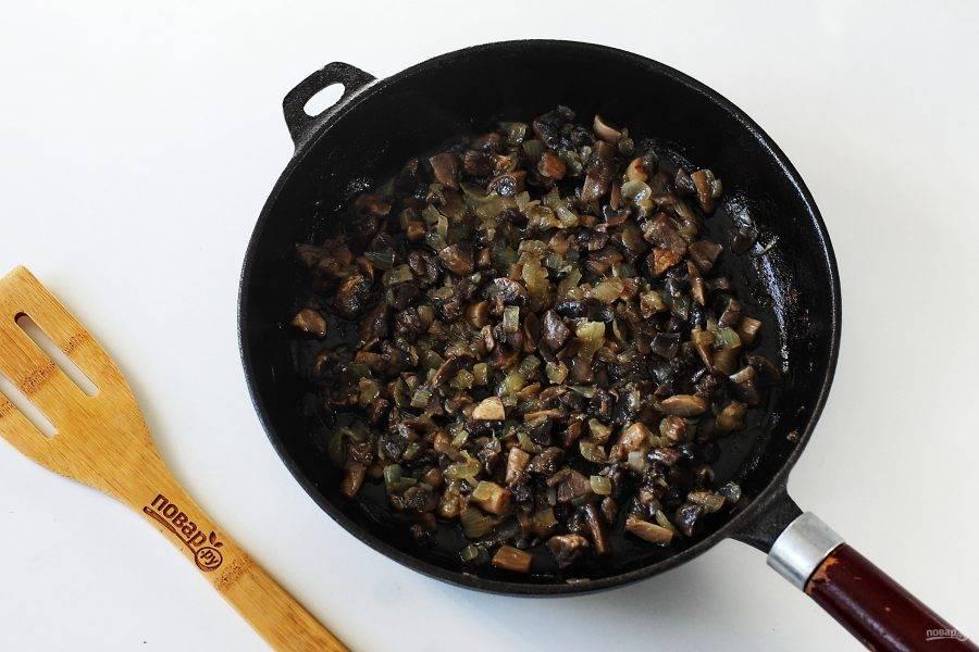 Одну луковицу нарежьте кубиками и обжарьте до мягкости. Добавьте измельченные ножом грибы и готовьте все вместе до испарения жидкости.