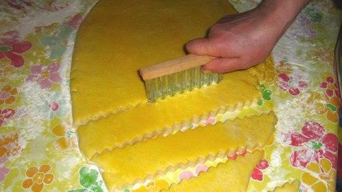 3. Рулет раскатываем скалкой, чтобы сделать его плоским. Смажем взбитым яичным желтком и разрежем эту лепешку фигурным ножом на печеньки.