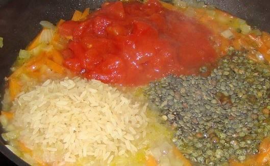 Добавьте рис, чечевицу и мелко порезанные томаты. Вливаем воду и добавляем чеснок (дольками) перец, соль и куркуму.