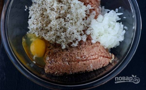 1. Первым делом отварите до полуготовности в подсоленной воде рис и остудите немного. Соедините его в глубокой мисочке с фаршем, яйцом, мелко нарезанным луком. Добавьте соль и перец по вкусу. Все как следует перемешайте.